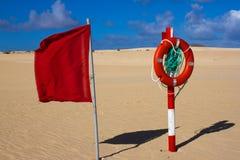 Круг заплывания Цвет томбуя жизни красный на пляже с яркой предпосылкой песка и неба 2 предупредительного знака Предохранитель бе Стоковое Изображение