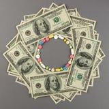 Круг созданный от покрашенных пилюлек с деньгами МЕДИЦИНСКАЯ принципиальная схема Стоковое Изображение RF