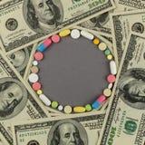 Круг созданный от покрашенных пилюлек с деньгами МЕДИЦИНСКАЯ принципиальная схема Стоковое фото RF