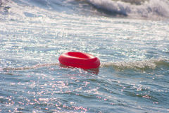 Круг спасения красный отбрасывая на море развевает Стоковое Фото