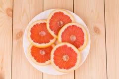Круглые куски грейпфрута на плите Стоковые Фото