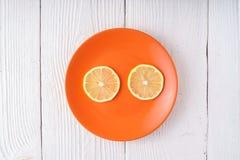 Круглые куски лимона на оранжевой плите Стоковое фото RF
