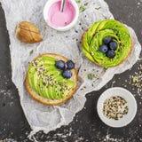 Круглые плюшки для завтрака с авокадоом в форме розы с соусом югурта с разнообразие seedsAgainst сезама Стоковая Фотография RF