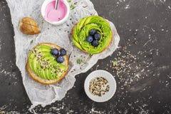Круглые плюшки для завтрака с авокадоом в форме розы с соусом югурта с разнообразие seedsAgainst сезама Стоковое Фото