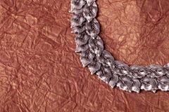 Круглый серебр выходит орнамент на салфетку скомканную золотом Стоковые Фотографии RF