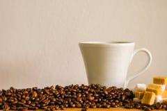 Кружка белого кофе с кофейными зернами и белизной и кубами желтого сахарного песка Стоковое Изображение