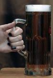 Кружка владением руки пива стоковые изображения rf