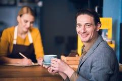 Кружка жизнерадостного мужского клиента выпивая жидкости Стоковые Фотографии RF