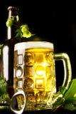 Кружка золотых пива, бутылки и openner с листьями хмеля Стоковое Изображение RF