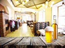 Кружка и бутылка пива на таблице Стоковые Фотографии RF