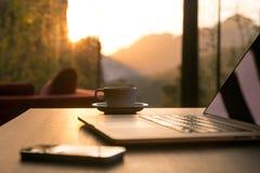 Кружка и телефон кофе компьютера на черной деревянной таблице греют на солнце поднимать Стоковые Фотографии RF