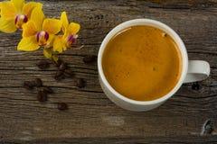 Кружка кофе и желтая орхидея на деревянной предпосылке Стоковая Фотография