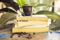 Кружка кофе, кофейные зерна и книги на деревянном столе Стоковое фото RF