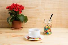 Кружка кофе, красные цветки, покрашенная конфета в опарнике и желтый dia Стоковая Фотография RF