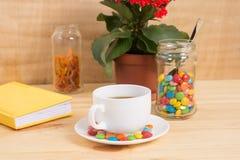 Кружка кофе, красные цветки, покрашенная конфета и апельсиновая корка в опарнике Стоковое фото RF