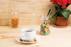 Кружка кофе, красные цветки, покрашенная конфета и апельсиновая корка в опарнике Стоковое Изображение RF