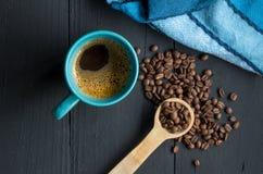 Кружка кофе на деревенском черном деревянном кухонном столе с кофейным зерном Стоковые Изображения RF