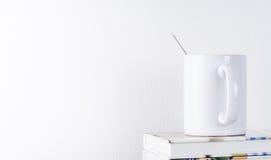 Кружка кофе на книге с белой предпосылкой Стоковое фото RF