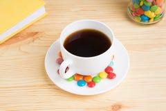Кружка кофе, покрашенная конфета в опарнике и желтый дневник на woode Стоковые Фото