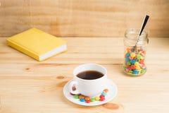 Кружка кофе, покрашенная конфета в опарнике и желтый дневник на woode Стоковые Фотографии RF
