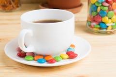 Кружка кофе, покрашенная конфета и апельсиновая корка в опарнике на деревянном Стоковая Фотография RF
