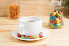 Кружка кофе, покрашенная конфета и апельсиновая корка в опарнике на деревянном Стоковые Изображения