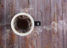 Кружка кофе помещенная на деревянном столе с горячим черным кофе Стоковые Изображения
