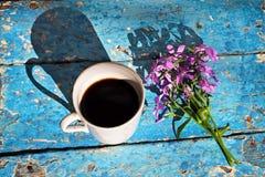 Кружка кофе с цветками на деревенской таблице Стоковые Фотографии RF