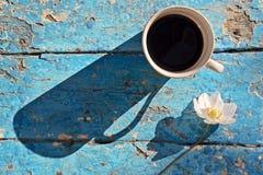 Кружка кофе с цветками на деревенской таблице Стоковое фото RF