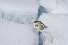 Кружка пешего туристского металла алюминиевая на береге Lake Baikal между льдом и снегом Стоковые Фото