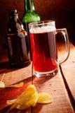 Кружка пива, бутылки и обломоки potatoe Стоковая Фотография