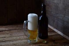 Кружка пива, бутылки на деревянной предпосылке Сфотографированный с естественным светом Стоковые Фотографии RF