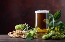 Кружка пива, зерна и хмелей на старом деревянном столе стоковое изображение rf