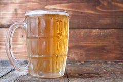 Кружка пива на деревенском деревянном столе Стоковая Фотография