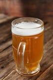 Кружка пива на темной деревянной предпосылке, конце вверх Стоковая Фотография