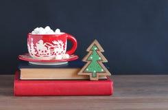 Кружка рождества красная на куче книг на темной предпосылке Стоковая Фотография RF