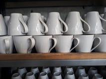 Кружка стекел для кофе на стеклянных полках Стоковое Фото