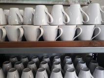 Кружка стекел для кофе на стеклянных полках Стоковая Фотография
