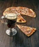 Кружка темного пива и кусок пиццы на деревянной предпосылке Стоковые Фото