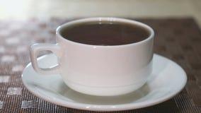 Кружка фарфора с черным чаем на таблице Пар приходя от кружки акции видеоматериалы