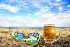 Кружка холодного пива на береге моря стоковое фото