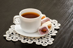 Кружка чая и турецкого наслаждения с гайками на плите, конца-вверх, черной предпосылки Стоковое фото RF