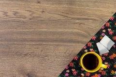 Кружка чая на салфетке ткани цветка картины на пустом деревянном backgroun Стоковое Изображение RF