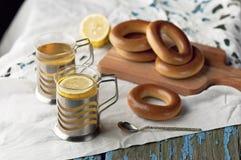 Кружка чая с бейгл на деревянной предпосылке Стоковые Изображения