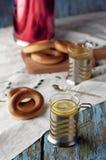 Кружка чая с бейгл на деревянной предпосылке Стоковая Фотография