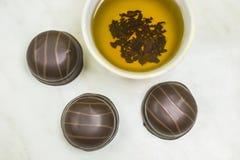 Кружка чая с десертом шоколада на светлой таблице стоковая фотография rf
