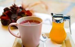 кружка чая ягод с медом и чайной ложкой на подносе и украшении стоковая фотография