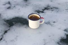 Кружка Enameled располагаясь лагерем путешественника с горячим чаем лаванды и пакетика чая на красивом сценарном льде в форме обл стоковые изображения rf