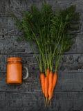 Кружка smoothie моркови и пук морковей на деревенской таблице взгляд сверху Плоское положение Стоковое фото RF