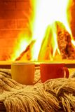Кружки для чая с шарфом шерстей против уютного камина Стоковое фото RF
